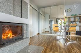 modernes wohnzimmer mit kamin tisch mit stühlen und kleiderschrank mit breitem spiegel