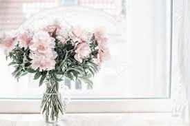 schöner pastell rosa blumenstrauß pfingstrosen in glasvase auf fensterbank blumen im wohnzimmer gemütliches zuhause