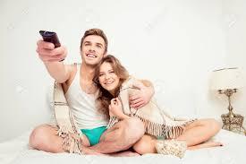 glückliches paar in liebe tv mit poporn im schlafzimmer mit karierten beobachten