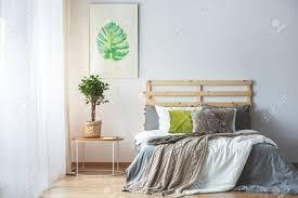 pastell schlafzimmer interieur mit grünen accessoires und monstera poster