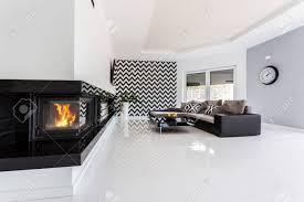 helle und geräumige luxuriöse wohnzimmer mit kamin großes sofa kleiner tisch und muster tapete