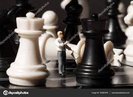 Chessman And Chess King Fall On Game Board Playing With Miniature Doll Macro Photo Man Explains Rules Teacher Puppet Chessboard
