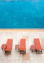 Empty Poolside Deckchairs With Beautiful Blue Swimming Pool From