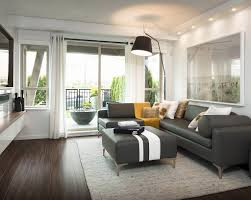 Impressive Gray Color Scheme Living Room Decorating Idea Features Cozy L Shaped Sofa And Modern Black Shade Arch Lamp Also Dark Brown Brick Parquet