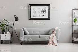 industrielle schwarz stehle und eine rosa decke auf ein elegantes sofa mit kissen in einem grauen wohnzimmer interieur mit platz für einen