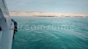 A Yacht In The Ocean With People On Board Against Background Of Rocky Desert Beach Diving And Fishing Side View Stock Footage