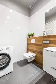 modernes grau weißes badezimmer mit waschmaschine wc und schrank