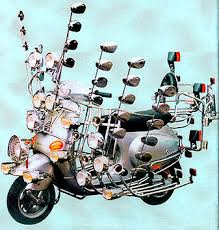 An Old Vespa Or Lambretta Loaded Up Almost Precariously So With Enough Mirrors To Fill A Medium Sized House Legshield And Handlebar
