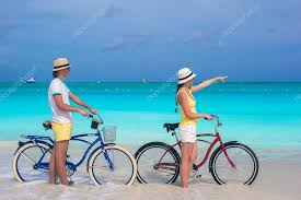 Young Happy Couple Riding Bikes On White Tropical Beach Stock Photo