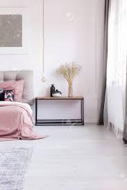 hölzerner nachttisch kunstwerk und kupferne pendelleuchte neben gemütlichem bett mit pinkfarbener bettwäsche