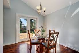 Pastel Blue Walls And Vaulted Ceiling Of American Dining Room Furnished With Glass Top Wooden
