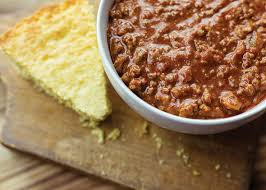 Bowl Of Chili With A Piece Cornbread On Wooden Background
