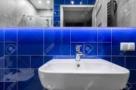 moderne badezimmer mit waschbecken spiegel und glänzende blaue fliesen