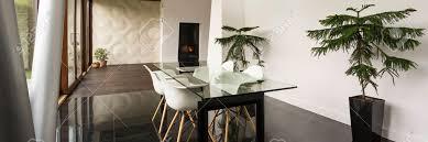 stilvolles esszimmer mit glastisch und weißen stühlen