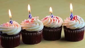 Four chocolate birthday cupcakes with blue candles burning HD stock footage clip