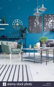 grüne sessel neben einem tisch mit anlage gegen blaue wand