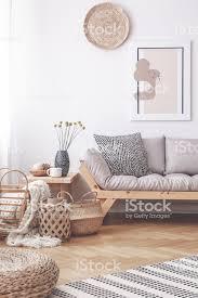 körbe und hocker auf holzboden im wohnzimmer interieur mit poster über grauen sofa echtes foto stockfoto und mehr bilder beige