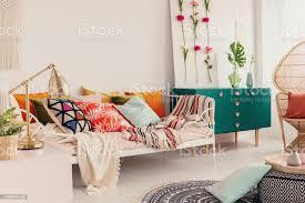gemusterte und bunte kissen auf metall einzelbett in stilvolle mädchen schlafzimmer innenraum mit pfau stuhl und schrank mit krone grün gestalten