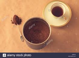 Container With Ground Coffee A Spoon Powder And Cup Of On Brown Paper Background