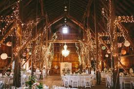 Twinkle Lights Strung On Branches At An Indoor Rustic Wedding Reception In A Barn