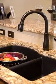 rubbed bronze faucets with a stainless steel sink kitchen bar