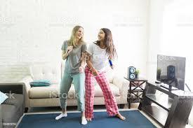 fröhliche frauen karaokesingen und tanzen im wohnzimmer stockfoto und mehr bilder das leben zu hause