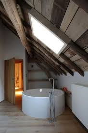 une salle de bain sous comble avec une baignoire îlot