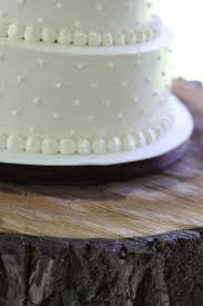 White Swiss Dot Wedding Cake On Rustic Wood Stand