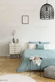 frühstück auf metall tisch vor einem bett mit salbei grün bettwäsche in einem natürlichen schlafzimmer inneren eine beige schublade schrank neben dem