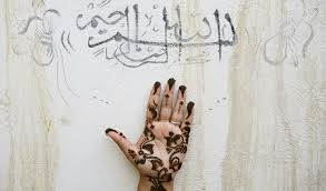An Iranian Woman Holds Up Her Hand Painted With Henna Under A Religious Sentence