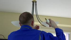 electrician changing light bulbs in chandelier at client home