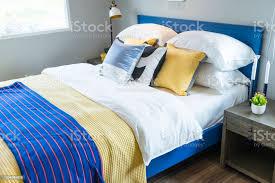 blaue und gelbe kissen auf schlafzimmerbett stockfoto und mehr bilder behaglich