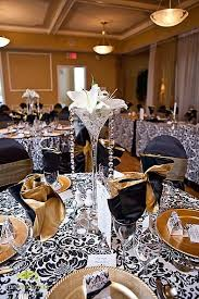 Gold plates and napkins paired with black damask table cloth