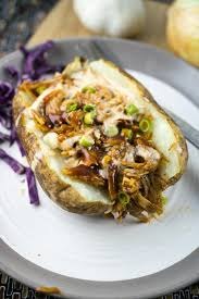 Baked Russet Potato On A White Plate Stuffed With BBQ Pulled Jackfruit Purple Cabbage