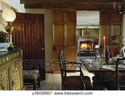 Victorian Lamp On Sideboard In Dining Room With Double Wooden Doors And View Of Fireplace Living