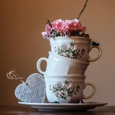 Three Teacups Stacked On Top Of One Another With Floral Patterns And Designs Them