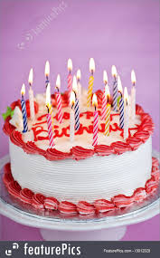 Celebration Birthday cake with lit candles and white icing