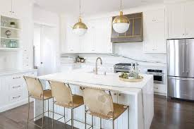 Delta Trinsic Kitchen Faucet Champagne Bronze by White Center Island With Gold Suede Counter Stools Transitional