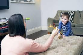 mutter spielt mit sohn und spielzeug wohnzimmer