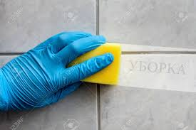 reinigungsschwamm in der gehalten während der reinigung badezimmer mit russischer beschriftung cleaning in englisch übersetzung