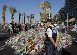 A Police Officer Watches People Gathering Around Floral Tribute For The Victims Killed During
