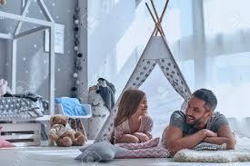 geheimnisse mit papa teilen vater und seine tochter die einander beim lü auf dem boden im schlafzimmer lächeln und betrachten