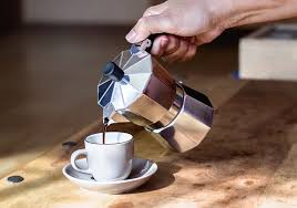 Womans Hand Holding Coffee Maker While Pouring On Cup
