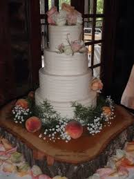 Four Tier Rustic Butter Cream Wedding Cake With Flowers Peaches And Wood Slab Stand