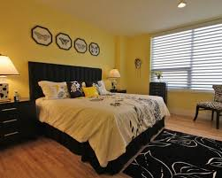 Example Of A Trendy Medium Tone Wood Floor Bedroom Design In Houston With Yellow Walls