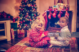Cute Girls Opening Presents In Front Of Christmas Tree Stock Photo