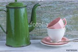 Vintage Green Coffee Pot And White Pink Cups On Rustic Background