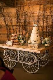 A Rustic Wedding Cake Table Made With Wagon Wheels And Branches Backdrop Buttercream