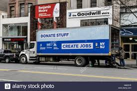 100 Goodwill Truck Two Employees Are Unloading A Truck Is Parked In Front Of