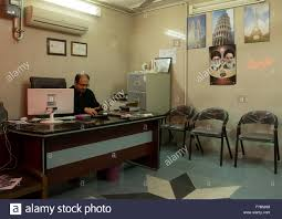 Man Working With A Computer In Travel Agency Office Khomeini Picture On The Wall Isfahan Province Kashan Iran